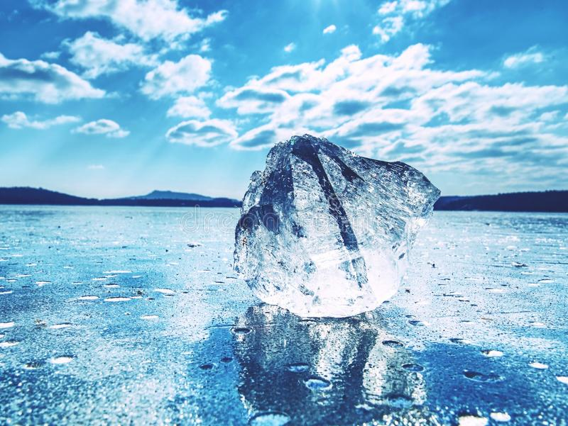 Ice shards on a frozen lake. The rays of the sun creat rainbow shadows. In the cracks of the ice stock image