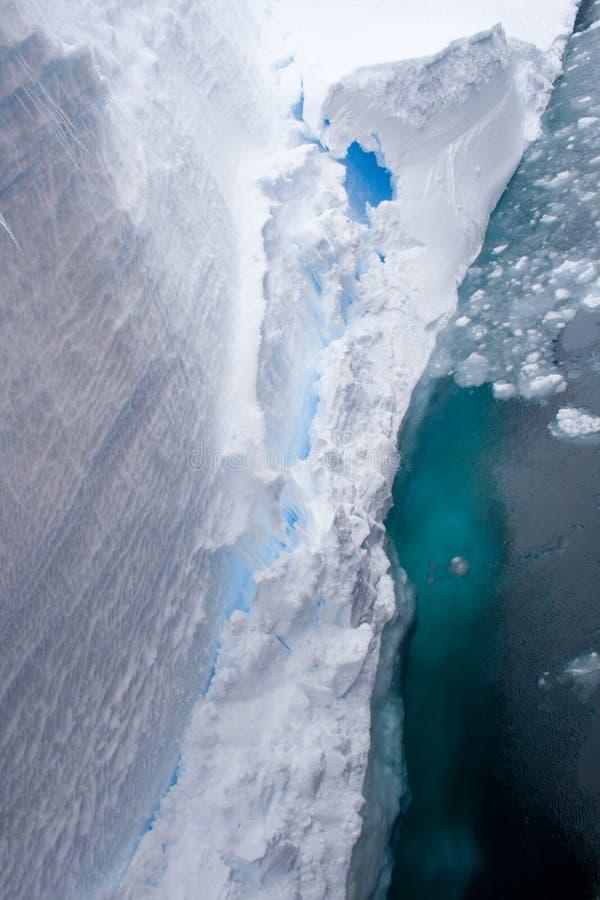 Ice Shelf Edge. The ice shelf of Antarctica drops off into the freezing near freezing sea water stock images