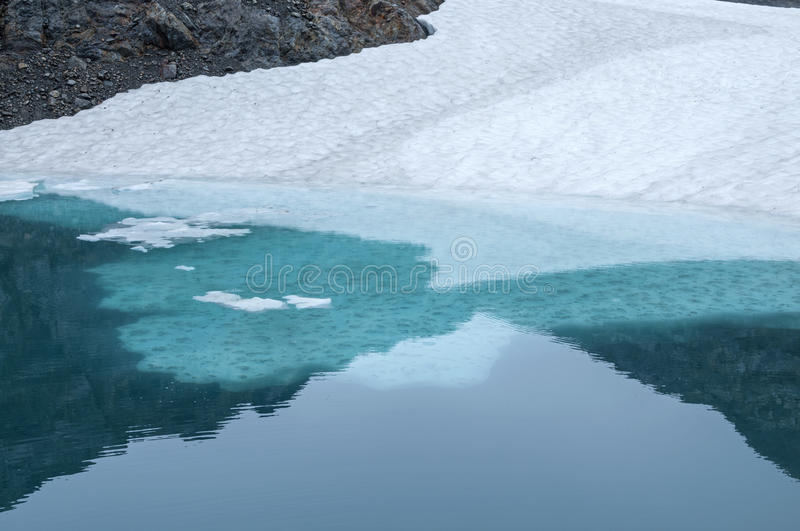 Ice shelf in glacial pool. Frozen ice shelf and snow in freezing cold glacial pool of meltwater stock photos