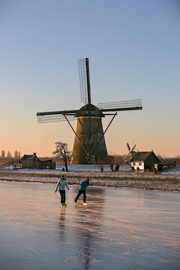 Free Ice Skater In Front Of The Kinderdijk Windmills Stock Photography - 214762742