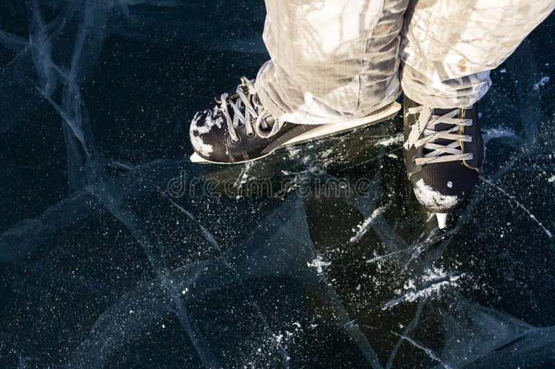 Ice skater`s skates covered with snow on the picturesque ice of Lake Baikal in winter during a sunny day. royalty free stock image