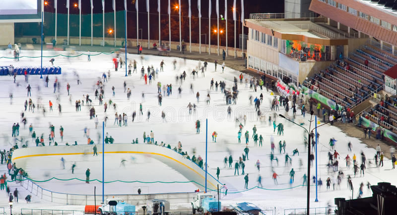 Ice skating rink whith motion blurred large group of skating peo stock image