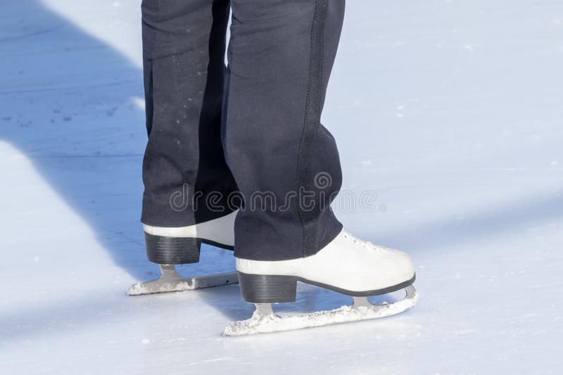Ice skating, woman legs wearing white leather skates, training on a frosen snowy skating rink in winter close up royalty free stock photo