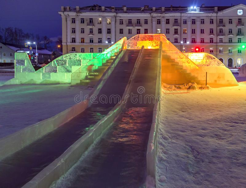 Ice slide collected from ice blocks. Two ice stairs lead to the top, from which you can go down two gutters. The backlight is produced with colorful lights stock photo
