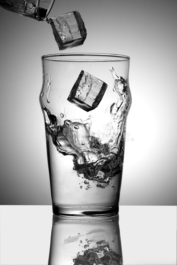 Ice Splashing Into A Glass Of Water Stock Image