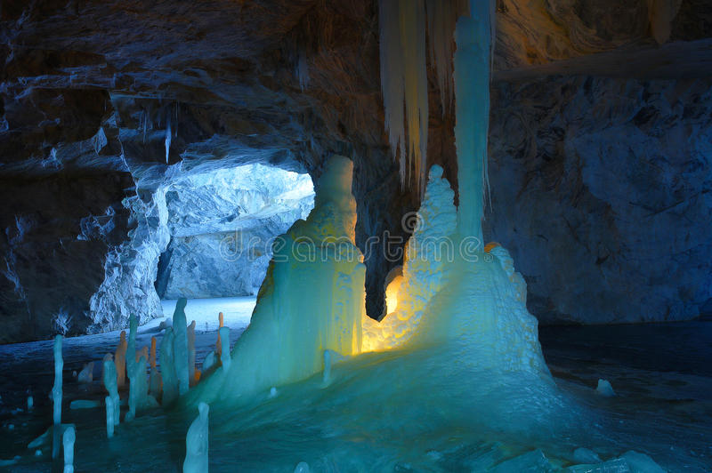 Ice stalagmites and stalactites illuminated by candles and fluorescent light inside the marble mine. Ruskeala, Karelia, Russia royalty free stock photography