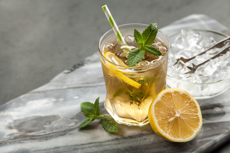 Ice tea with lemon and mint. Grey backround stock images