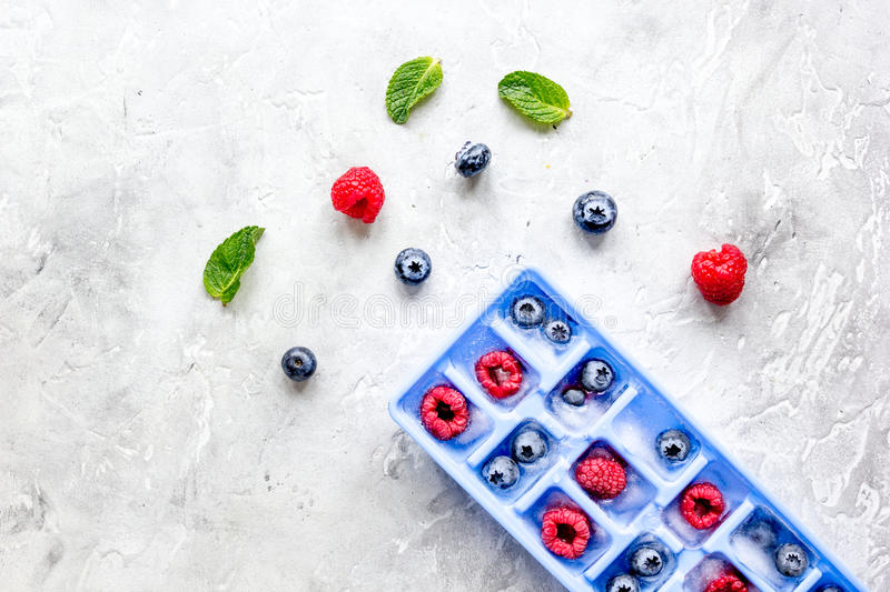 Ice tray with berries and mint on stone top view mock up stock image
