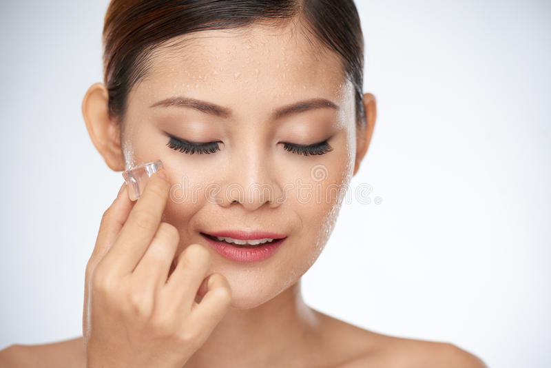 Ice treatment. Young Asian woman rubbing face with ice cubes stock photo