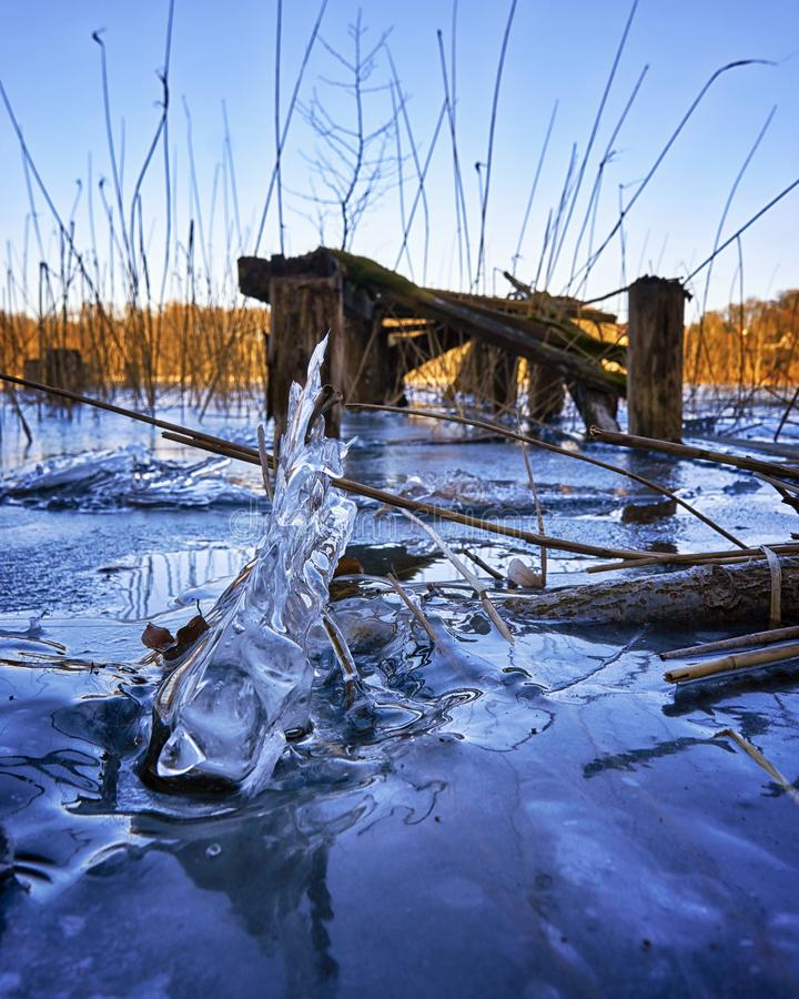 Ice waves on frozen lake with bridge in the background. The ice is crystal clear stock photography