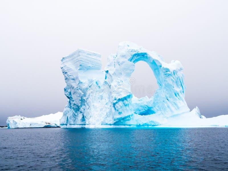 Iceberg arqué dans le cimetière d'iceberg de baie de Pleneau à l'ouest de la fourmi photographie stock