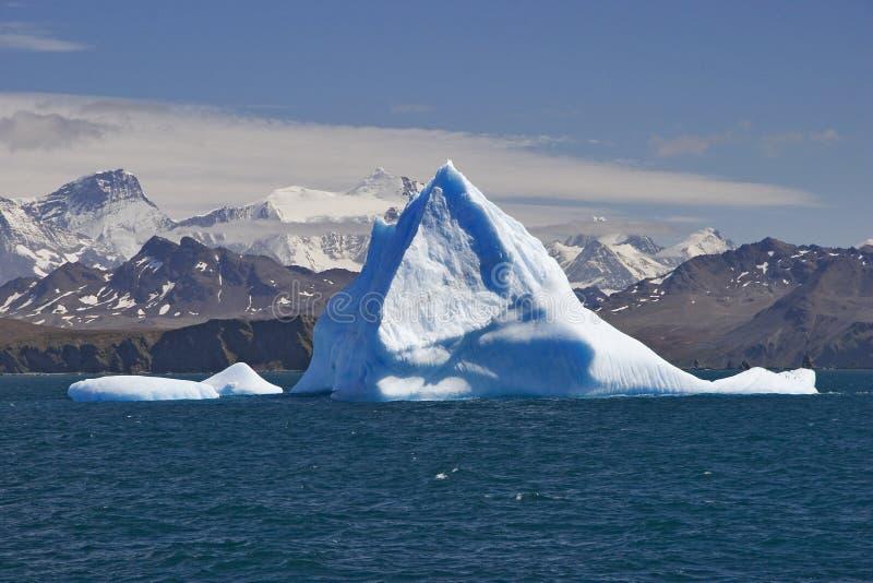 Iceberg azul com terra fotografia de stock royalty free