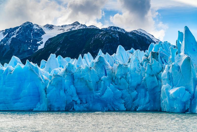 Iceberg blu di Gracier grigio con la bei montagna e lago grigi fotografia stock libera da diritti