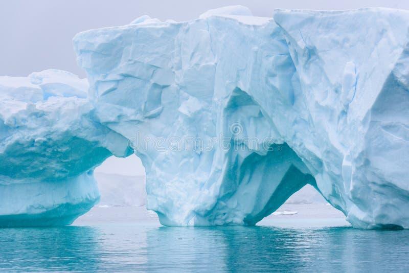 Iceberg bonito do azul de turquesa que flutua no ant?rtico, contra um fundo nevoento fotos de stock