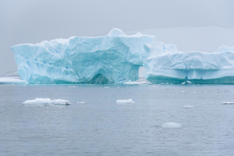 Iceberg bonito do azul de turquesa que flutua no ant?rtico, contra um fundo nevoento fotografia de stock royalty free