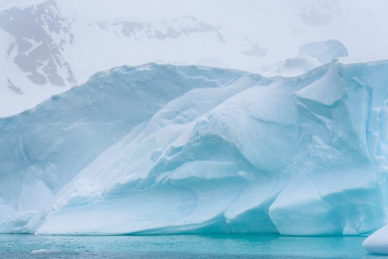 Iceberg bonito do azul de turquesa que flutua no ant?rtico, contra um fundo nevoento imagens de stock