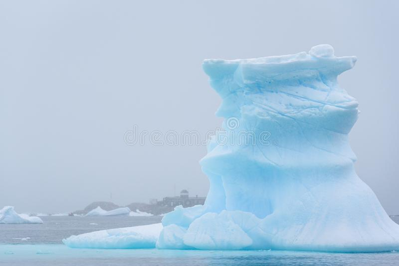Iceberg bonito do azul de turquesa que flutua no ant?rtico, contra um fundo nevoento com uma esta??o de pesquisa fotografia de stock