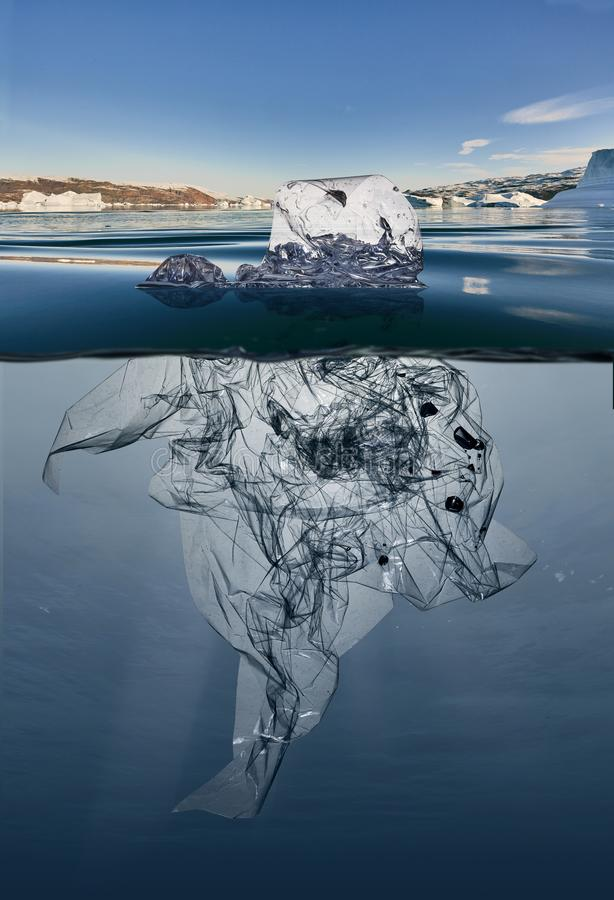 Iceberg do plástico do lixo que flutua no oceano com greenland para trás foto de stock