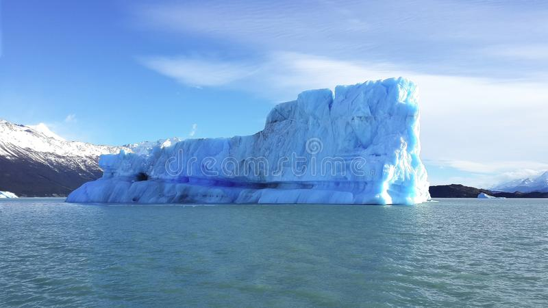 Iceberg or ice mountain is a large piece of freshwater ice that has broken off a glacier or an ice shelf and is floating freely in. Open water royalty free stock photography