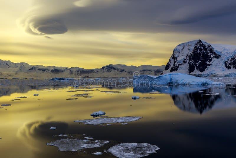 Iceberg, montagnes bleues et coucher du soleil se reflétant dans l'océan chez Lemair images libres de droits