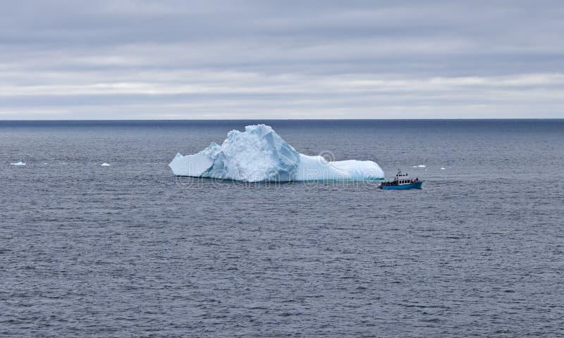 Iceberg with sightseers, Newfoundland. Sightseeing boat passes large iceberg off the coast of St. Anthony, Newfoundland and Labrador, Canada stock photo