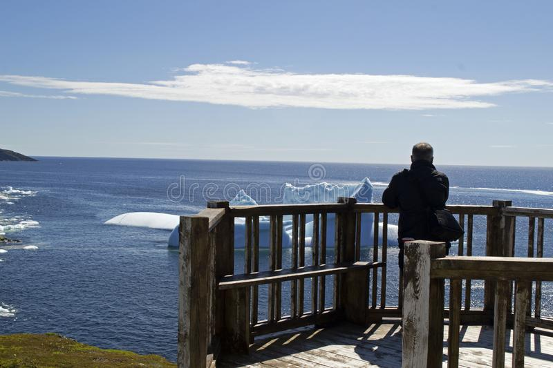 Tourist enjoying the view Iceberg Alley Fishing Point St. Anthony NL. Iceberg watching on a beautiful sunny day Iceberg Alley St. Anthony Newfoundland royalty free stock photo