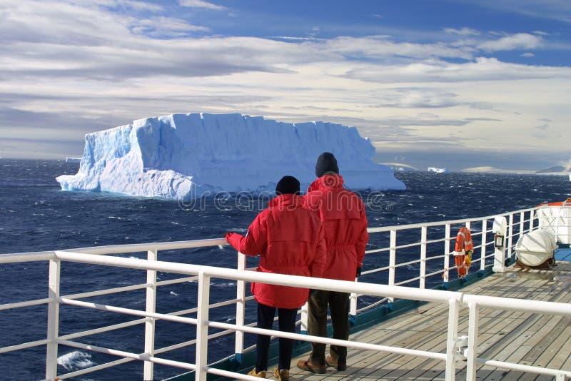 Iceberg watching. Passengers looking at gigantic iceberg from a cruise ship royalty free stock image