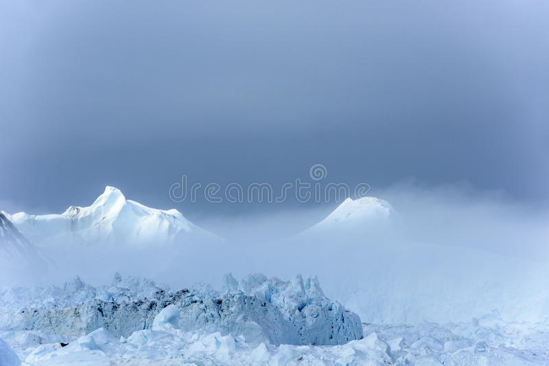Sun breaking through fog on Icefjord Ilulissat, Greenland. Beautiful icebergs coming out of mist in Icefjord of Qeqertarsuup tunua - Ilulissat, Greenland royalty free stock image