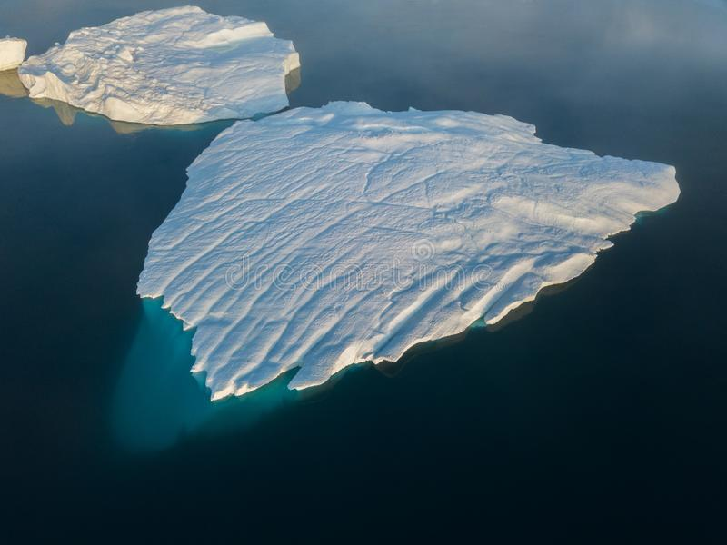 Icebergs drone aerial image top view - Climate Change and Global Warming. Icebergs from melting glacier in icefjord in Ilulissat. Icebergs drone aerial image stock image