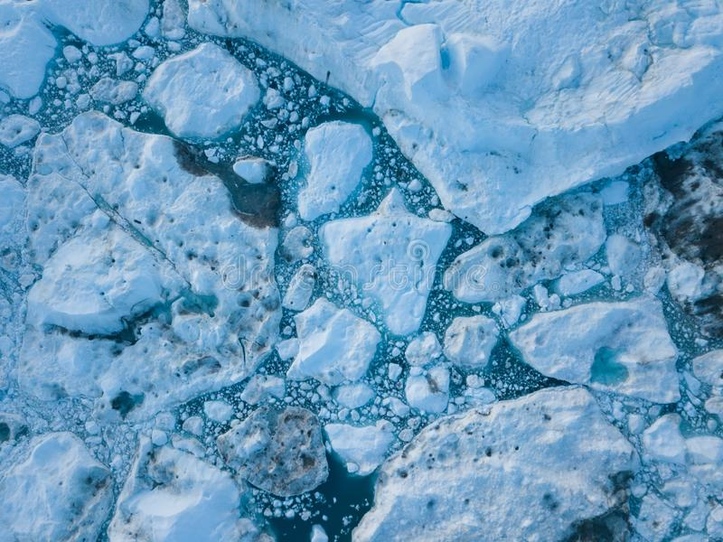 Icebergs drone aerial image top view - Climate Change and Global Warming. Icebergs from melting glacier in icefjord in Ilulissat. Icebergs drone aerial image stock photo