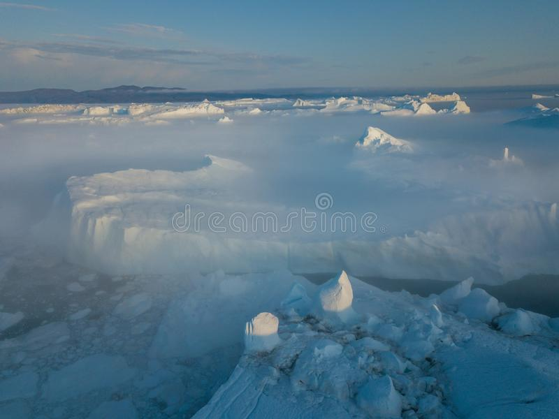 Icebergs drone aerial image top view - Climate Change and Global Warming. Icebergs from melting glacier in icefjord in Ilulissat. Icebergs drone aerial image stock photography