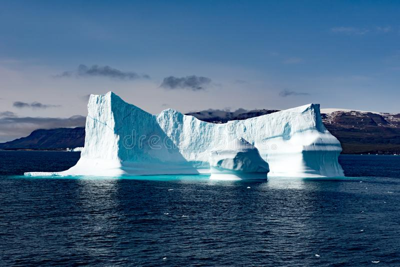 Icebergs in front of Seashore with snow covered Mountains, Greenland. Huge Iceberg building with tower. Beautiful turquoise and blue iceberg near Ilulissat royalty free stock photo