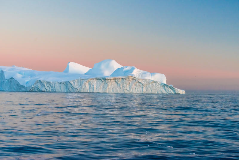 Icebergs in the midnight sun, Ilulissat, Greenland. Huge stranded icebergs at the mouth of the Icejord near Ilulissat at midnight, Greenland royalty free stock photography