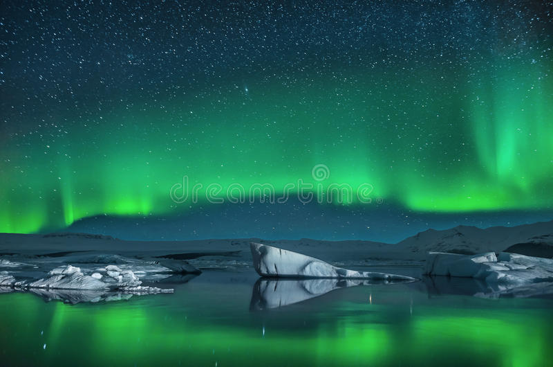 Icebergs under the Northern Lights. Northern Lights over the Jokulsarlon Glacier Lagoon in Southern Iceland royalty free stock photography