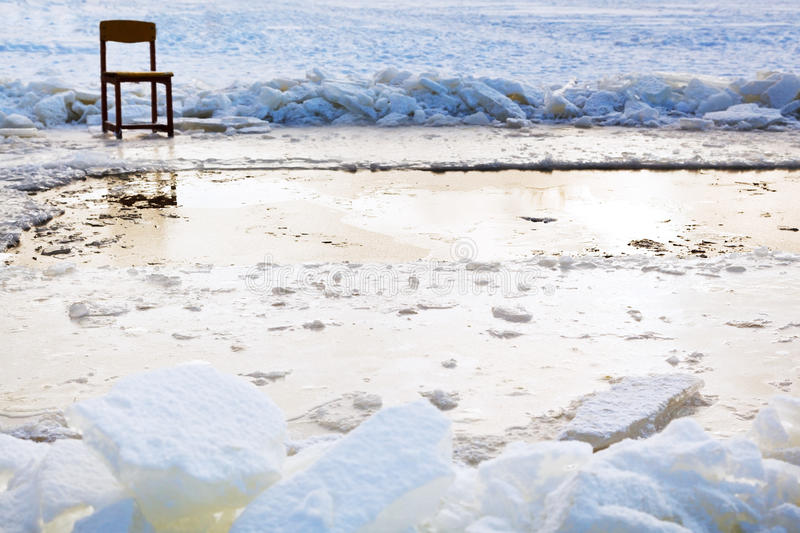 Icebound chair near ice hole in frozen lake. In cold winter day stock image