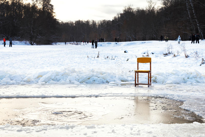 Icebound chair near opening water in frozen lake. After orthodox epiphany holiday in cold winter evening stock images
