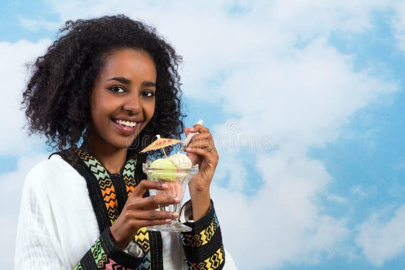 Icecream African girl. Happy Ethiopian girl wearing a traditional costume eating icecream stock images