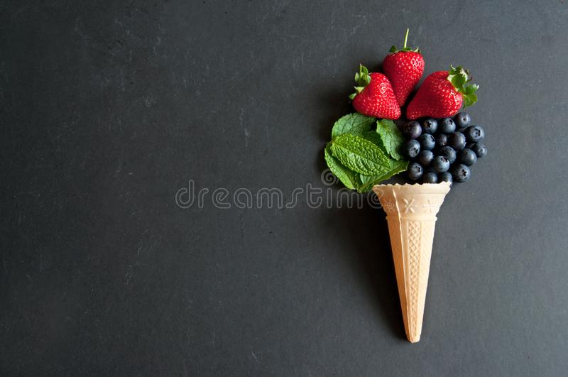 Icecream cone concept. Natural ingredients spilling out of an icecream cone including strawberry, mint and blueberries royalty free stock photo