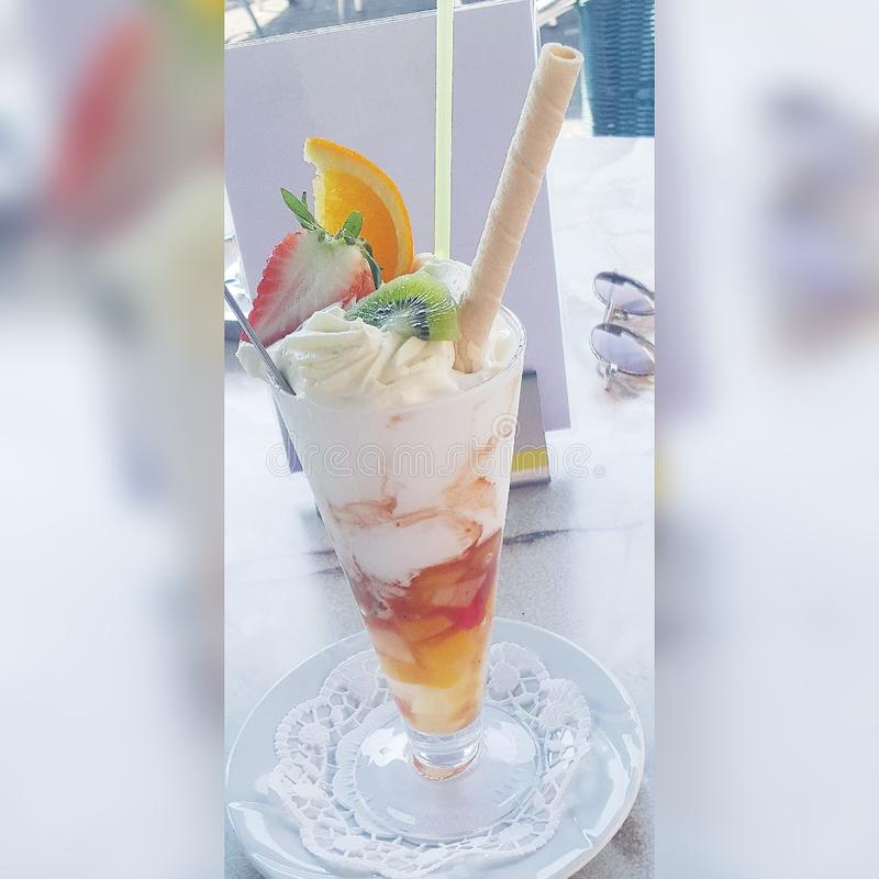 Icecream. At a icecream shop , icecream with fruit and Whippedcream and a straw royalty free stock photos