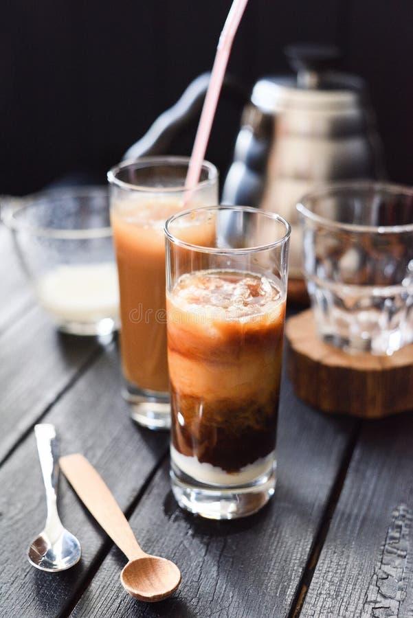 Iced分层了堆积咖啡用在高玻璃的椰奶在黑背景 免版税库存图片