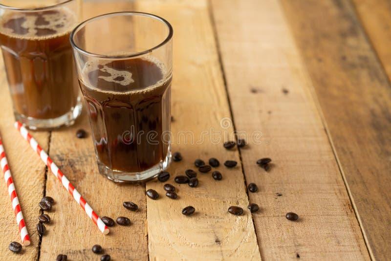 Iced在大透明玻璃的冰冻咖啡,倾吐在牛奶,与在木背景的咖啡豆,夏天冷饮, 免版税库存照片