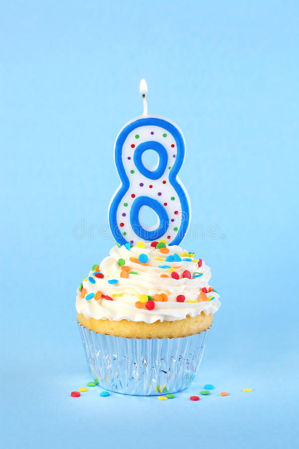 Iced birthday cupcake with with lit number 8 candle. And sprinkles stock images
