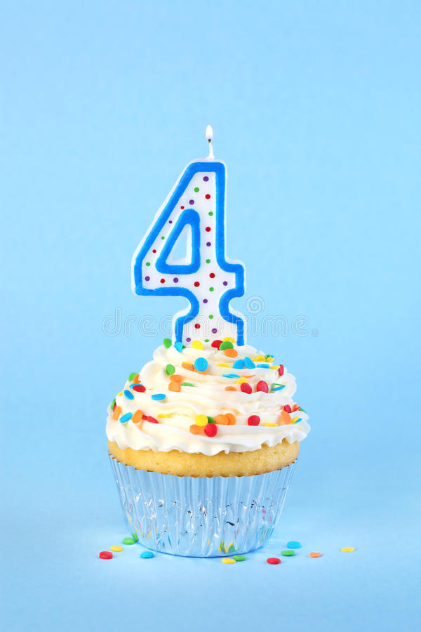 Iced birthday cupcake with with lit number 4 candle. And sprinkles royalty free stock photos