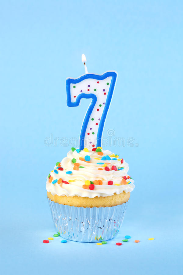 Iced Birthday Cupcake With With Lit Number 7 Candle Stock