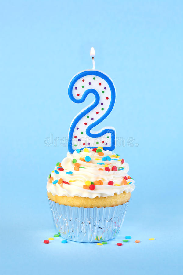 Iced birthday cupcake with with lit number 2 candle. And sprinkles stock photo