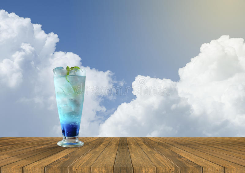 Iced blue italian soda fresh juice on Empty wood table and beautiful blue sky and cloud in background.summer fresh concept.drink royalty free stock image