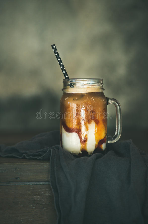 Iced caramel macciato coffee with milk in jar, copy space royalty free stock image