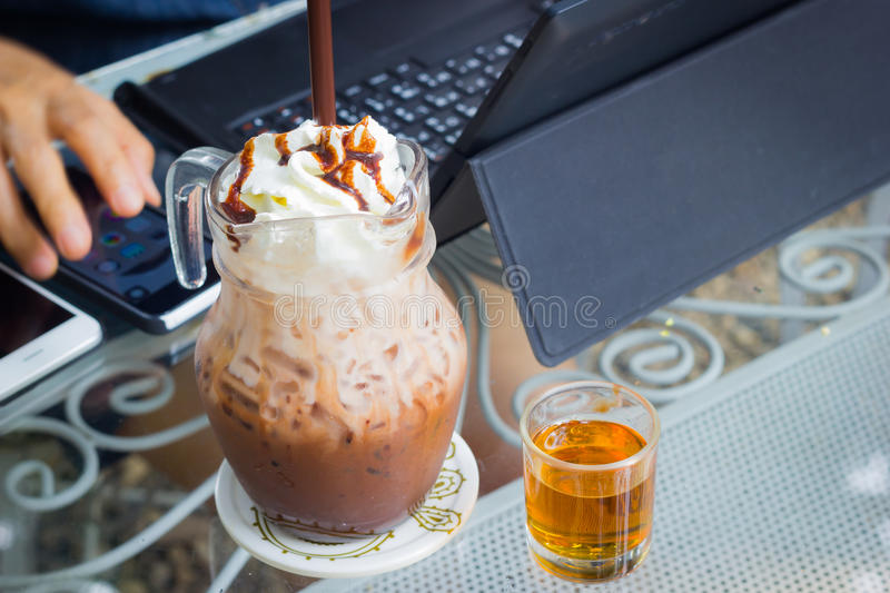 Iced chocolate milk with whip cream on the background of blurre. D hand using computer, business concept royalty free stock photo
