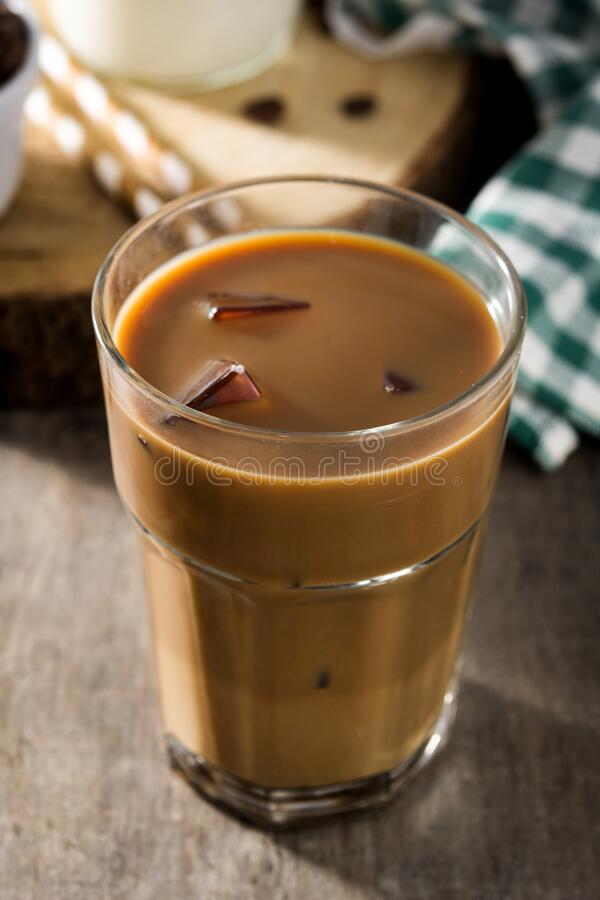 Iced coffee or caffe latte in tall glass. On wooden table stock images
