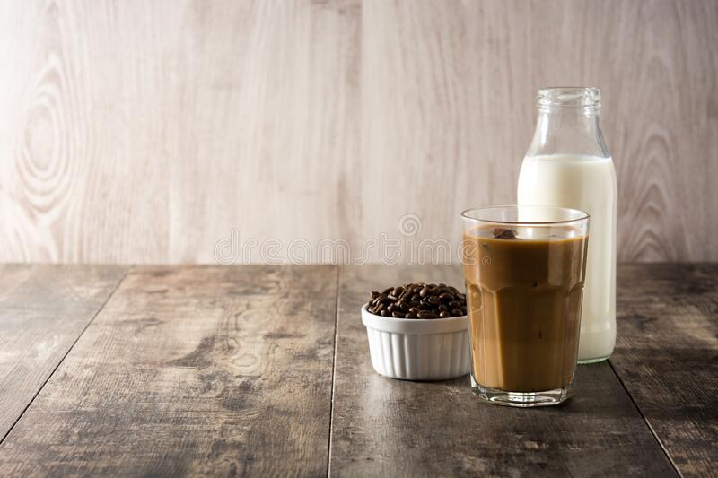 Iced coffee or caffe latte in tall glass. On wooden table. Copy space stock photo